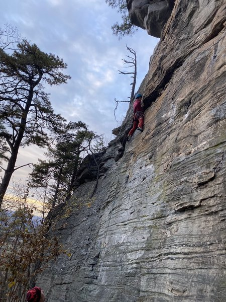 Erica attempting to chalk up before the crux