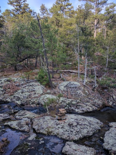 4) After bushwhacking, you can pass over the creek. Some cairns mark the spot to cross and the start of the faded climber's trail.