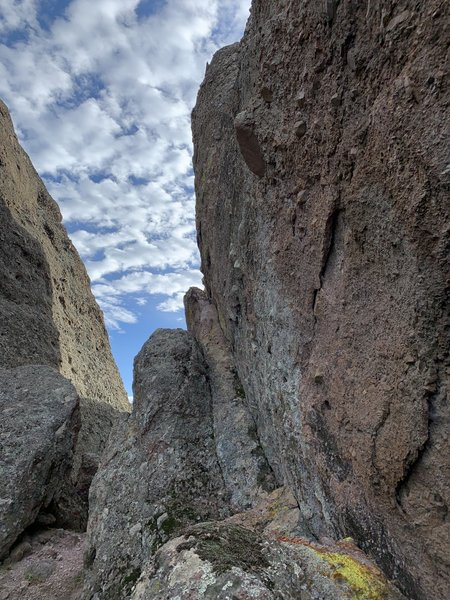 """View of the small ledge as seen from the direction of the intermediate anchor at the top of the face. The first bolt was in reach for me standing (5'5""""), second bolt was definitely a tougher move that the face, third bolt after reaching notch."""