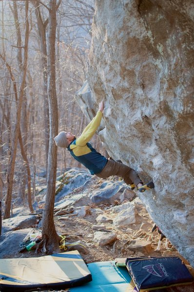 Evan Curry eyeing the sloping top-out of Lost Cause (V5).