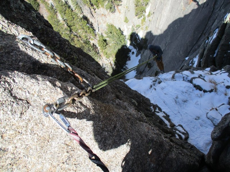The first rappel goes down the gully to the west. Look for the bolted station just down and west from the summit.
