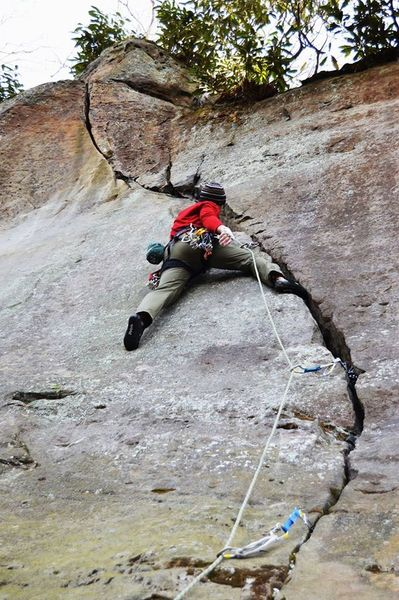 Approaching the first crux on Wandering Crack. Smear left foot on tiny nub on face, jam hands or lie back to step up to a good stance.