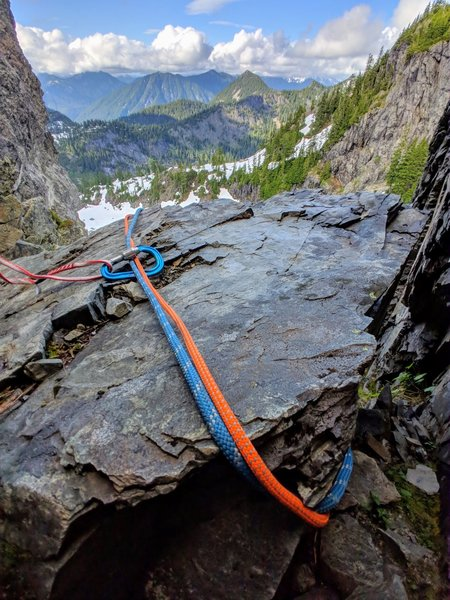 """Slung block for 2nd """"rap station"""" for direct descent from Pineapple pass. Cord only held on by tiny, razor sharp nub on back of boulder, otherwise it would slide off. Did not use, and do not recommend. Used slung tree to the north of the gully instead."""