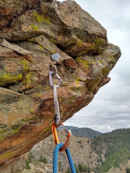The anchor placard points to a trad anchor above for belaying follower from top. Use the rappel anchors to climber's left for rappel.