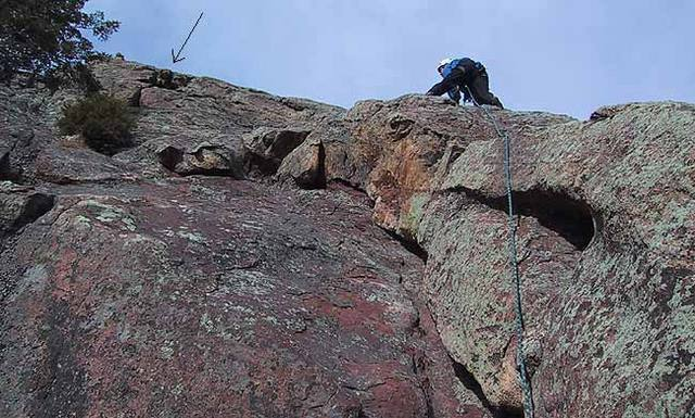 Warren Teissier running it out on the second pitch of the East Face of the Finger Flatiron.  Arrow marks the crux crack of the climb (note also the prominent tree).