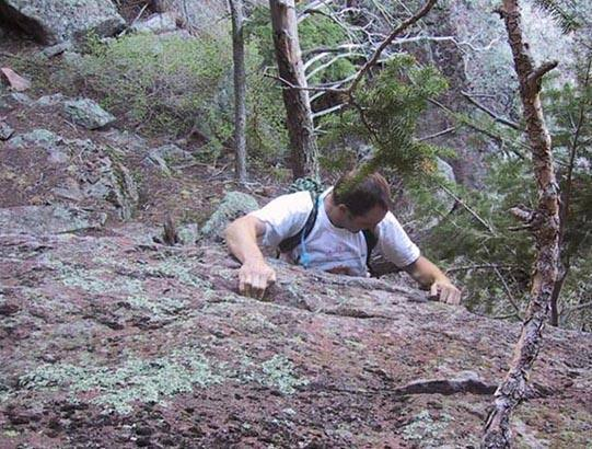 Scott executes the crux move on the secret downclimb.