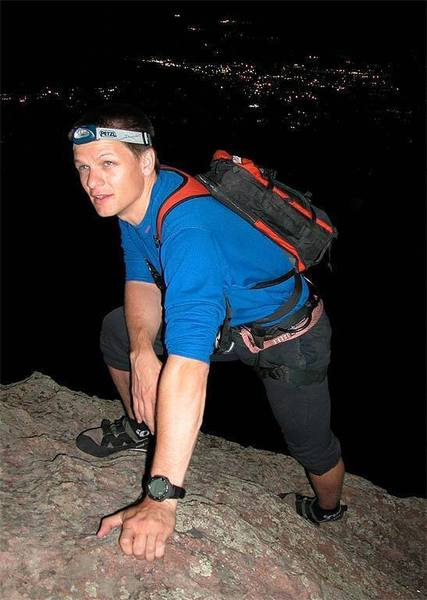 John reaches the summit on a moonlight ascent with the lights of Boulder behind.