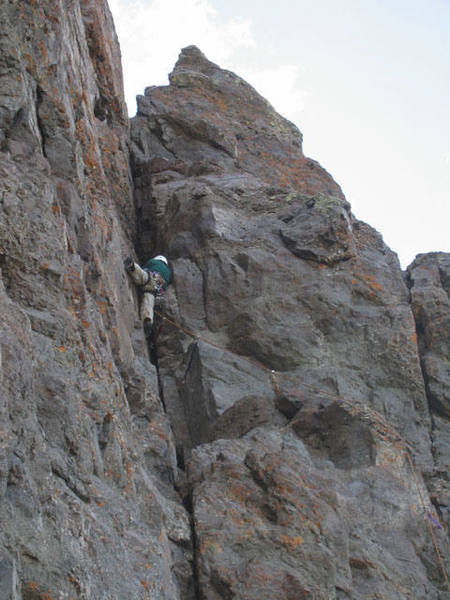 Moving through the chimney to the steep face on the left on the first pitch.