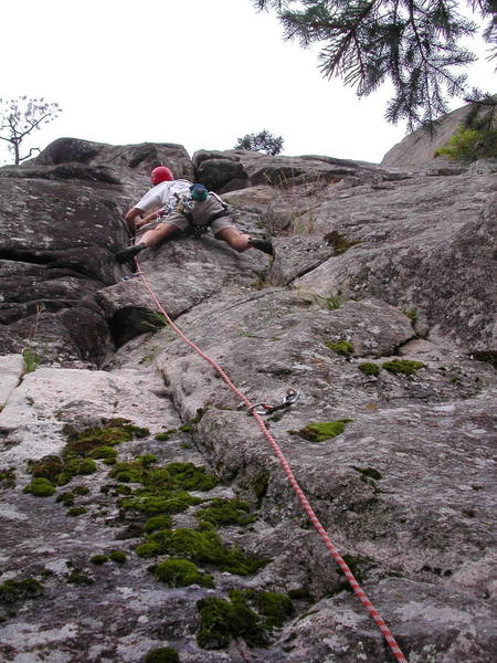 Scott Conner starting up the hand crack.  The crux roof looms above.