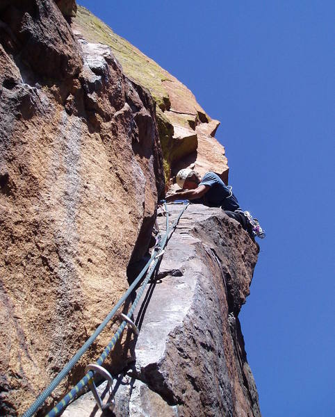 Finishing the scary move right around the arete to get to the hand crack on pitch 5.