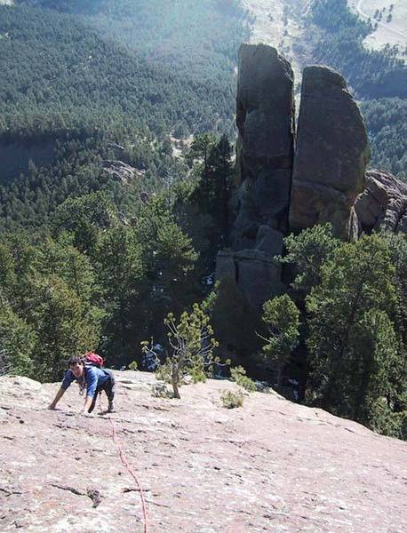 Warren climbing above the highest tree, with the chimney splitting Green Mtn Pinnacle obvious below.