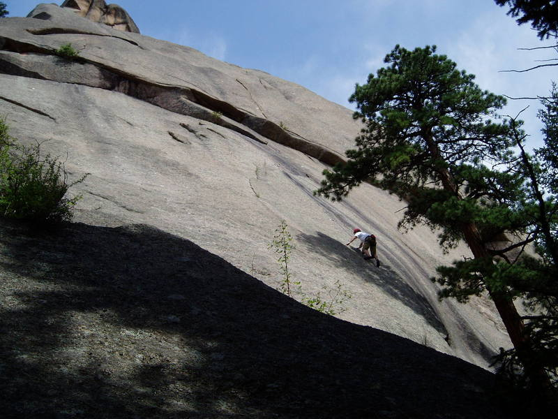 Luke following at the crux at the 5th bolt. From the 6th and last bolt, visible above Luke, you diagonal left to the thin left-facing flake.<br> <br> Two Jews Blues climbs the roof above near the far left of the photo. The first tier is climbed at the very edge of the photo, and the second tier is climbed just left of the bush. From there the route angles left and up to a belay right of the tree at the top left corner of the photo. Then straight right and up the rounded arete.<br> <br> Craggy Tur climbs the nice looking thin crack above the roof near the center of the photo. The crack apparently closes off at one point, since there is a bolt there. This is the 10c crux of that route.<br> <br> To the left of Craggy Tur is a nice looking pillar through the roof. There is a line of bolts up to and along the left side of the pillar and over the roof. I don't know what that line is.<br> <br> There is an 11c bolted line to the right of Luke that shares the first 2 bolts of this route and then cuts way right and up right of the black streaks.