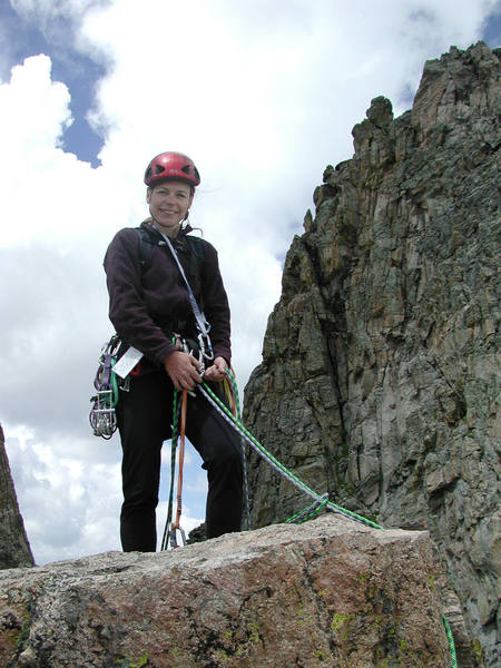 Christa Cline on the summit with The Saber in the background.