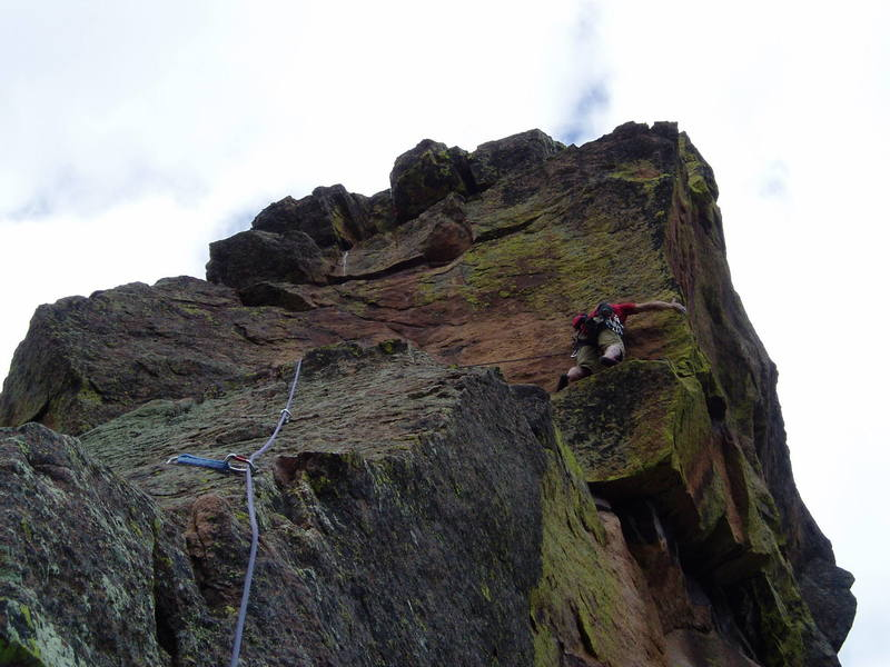 At the arete, if you're tall enough, you can maneuver your feet and reach up to a one joint finger hold. Then traverse left back to the 3rd bolt along the slightly rising thin horizontal crack. If you're too short, the move at the arete must be pretty hard. In any case, a fall from here would be ugly, since the bolt is about 10' to the left.