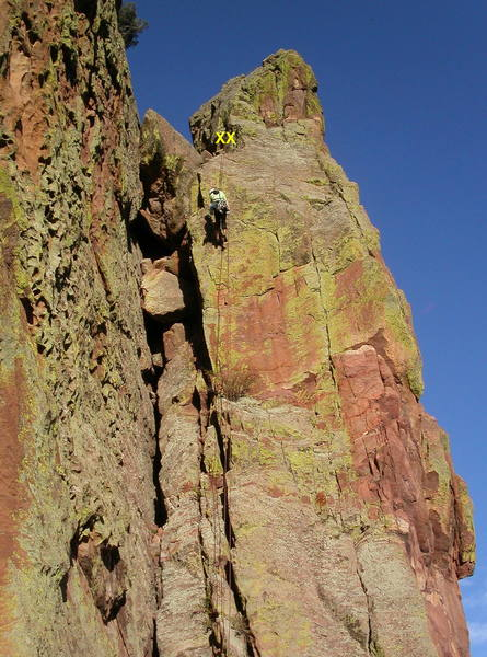 Chockstone Chimney rappel route.  From the top of Upper Ruper, scramble uphill to a wide notch, then down the other side to two huge bolt hangers on the left wall of the chimney.  A 100' rappel with a 60m rope takes you to the Upper Ramp; watch the ends of the rope.<br> <br> To descend from here, go around the right (N) side of a short slab and traverse left on a ledge to the rappel tree for the Upper Ramp (Vertigo) rappel route.  See the photo on the Redgarden Wall page for details.<br> <br> The pocketed wall to the left is Body Tremors; around the corner to the right is Italian Arete.