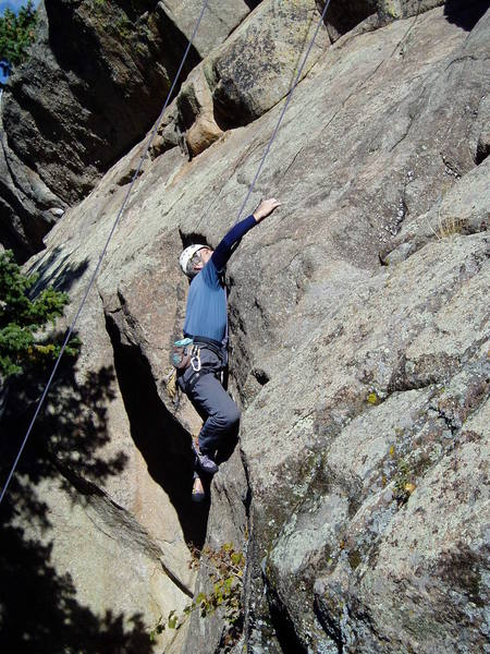 Reaching the good hold on the slab above the initial headwall.<br> <br> Photo by Paul Rezucha.