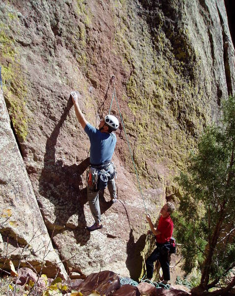 Starting the crux sequence. Thin feet lead to a good hold above Chuck's left hand. More thin feet but good hands lead to a good stance to clip the second bolt which is above the top of the photo.<br> Like Clarke is belaying.