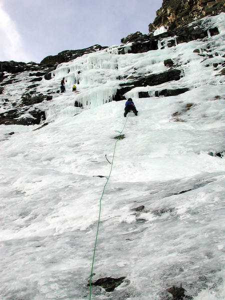 Christa leads up the first pitch avoiding ice fall from climbers above. Our line climbed straight up the steep ice to the right of the other party.
