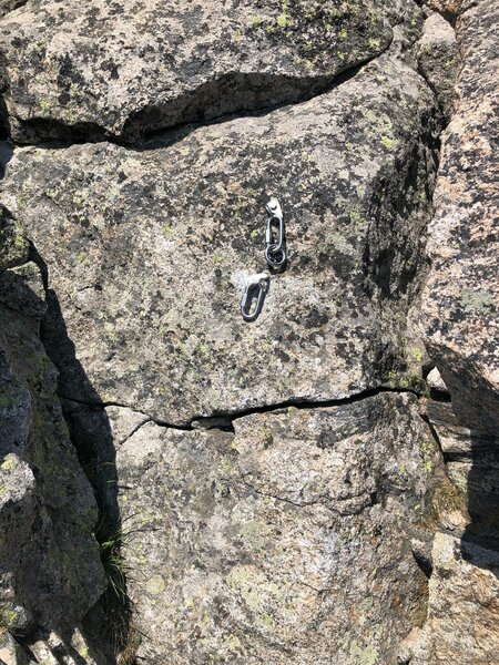 The summit rappel rings, which are a short downclimb from the summit in an alcove.
