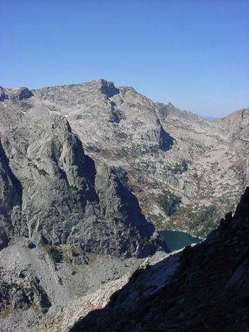 From the west side of Shoshone Peak: The North Face route diagonals left across the tree-covered bench into the shadowy cleft splitting the face.