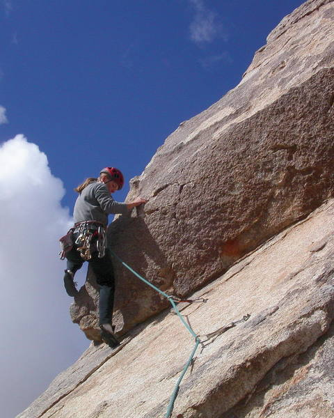 Christa Cline making the step onto the arete.