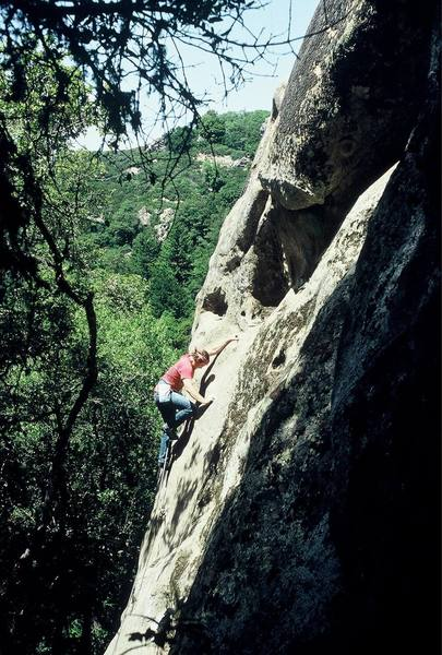 """Climber completing the 5.10c slab crux before confronting the final 5.11a roof of """"Putrefaction"""" (5.11a), Castle Rock Falls, CRSP, California"""