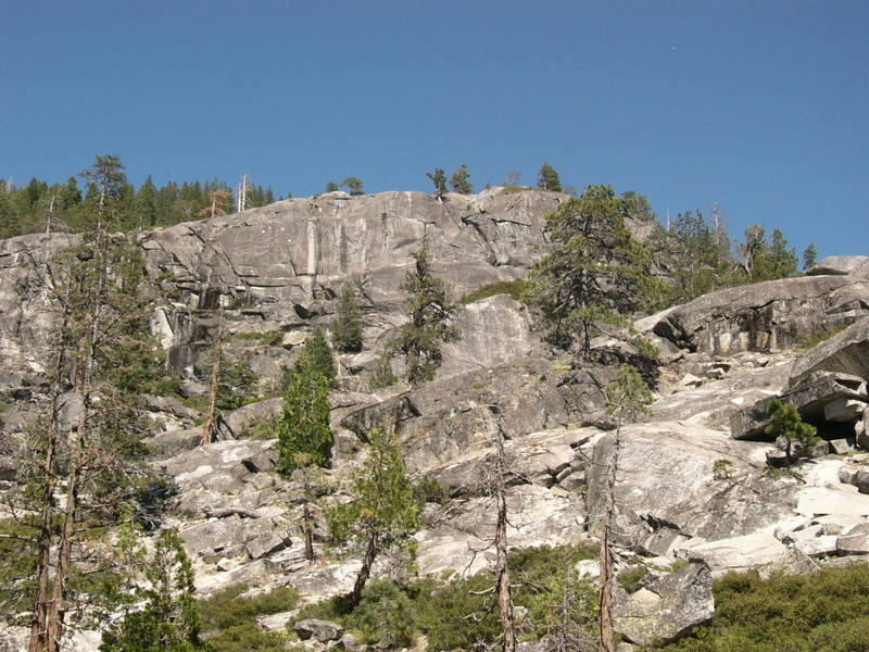 Shot of Indian Springs shown from the parking lot.  The Upper Tier is quite obvious with climbs right and left of the large white streak.  The Middle Tier is the slightly darker gray section under the right side of the Upper Tier behind pine tree.  The Lower Tier partial view is the roundish whiter rock below the right side of the Middle Tier.  The Upper Tier has 3 good routes further to the left outside of this photo.