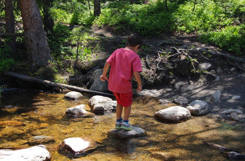 Alex hops across a creek