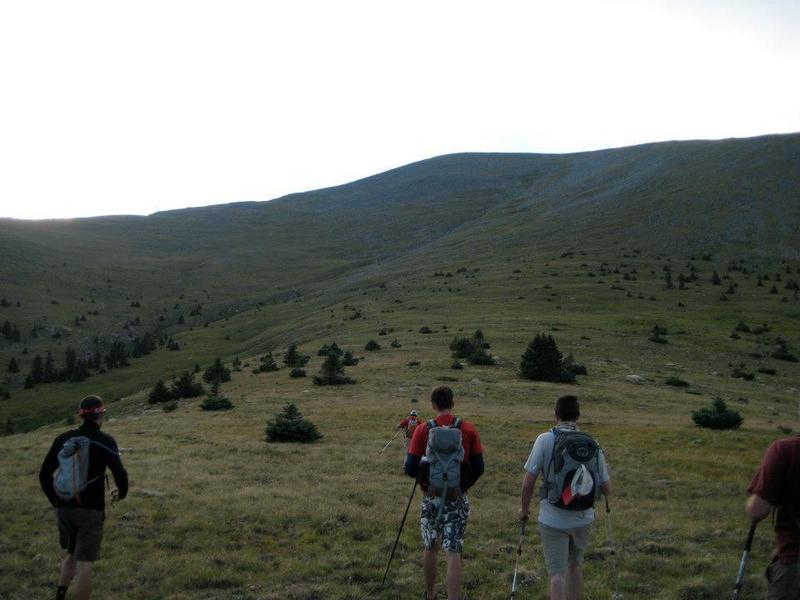 Hiking along the grassy slope toward the ridge. The drainage can be seen to the left.