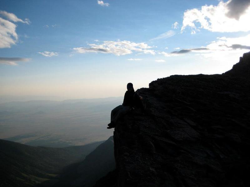 A daring hiker sits on the NE edge of the summit. This part of the summit need not be climbed and is easily avoidable for those afraid of heights.