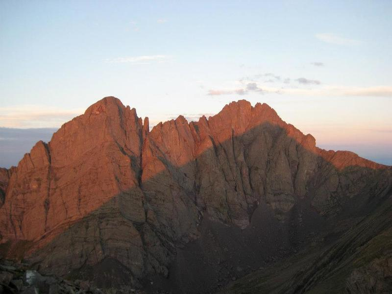 A stunning view of Crestone Needle (left) and Crestone Peak (right), with morning alpenglow above the shadow of Humboldt Peak.