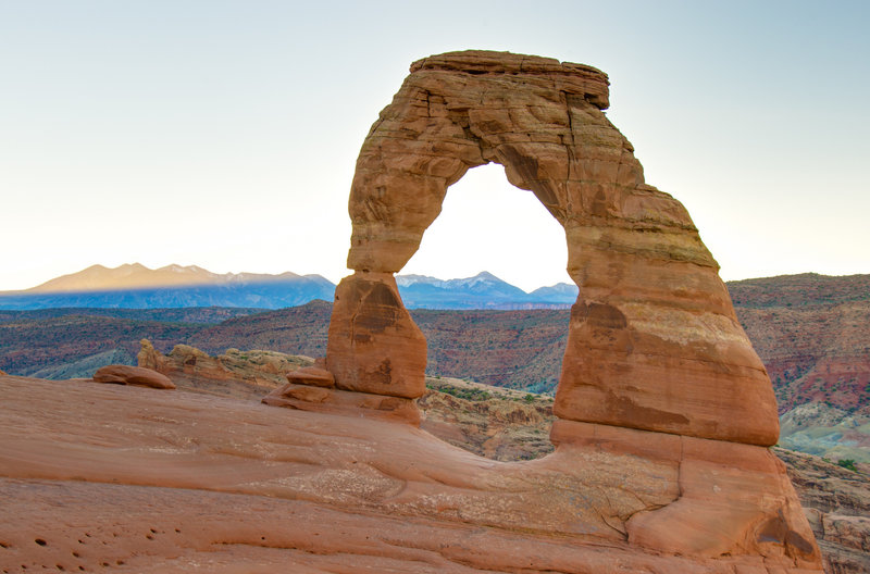 Delicate Arch at sunrise with La Sal Mountains