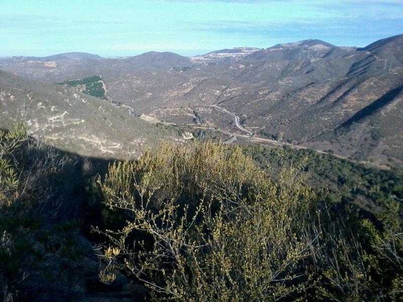 """Looking back down to the ranger station. You can see """"The Way Up"""" trail zig-zagging up the sunlit slope on the left."""