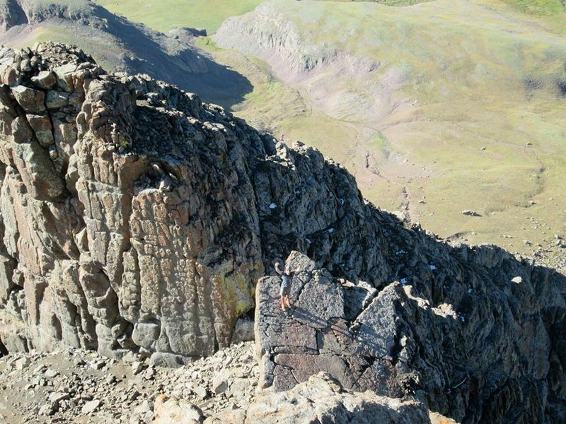 A hiker approaches the summit block. The technical formation behind him is not a part of this hike. There are many excellent scrambling options in this area. Have fun, but be careful!