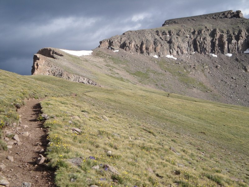 The trail up Uncompahgre Peak. The summit is visible to the right; your goal is to hike to the left of this massif before traversing behind it to the top.