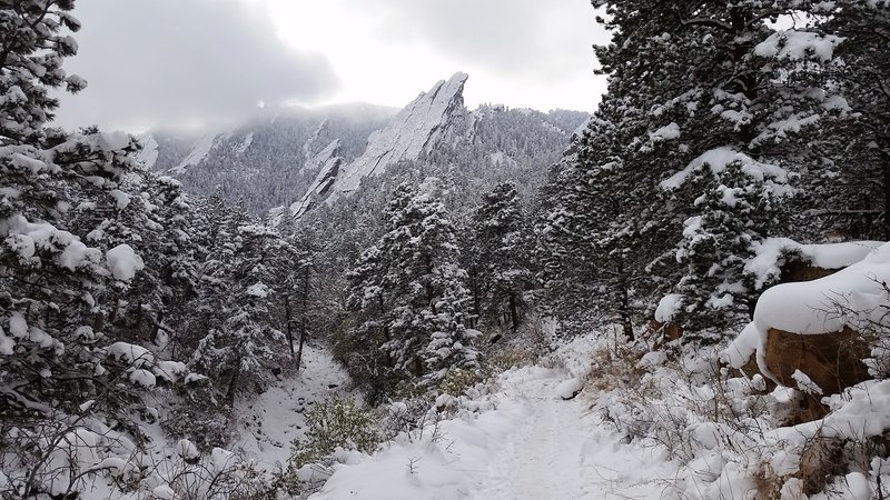 A snowy start of the Mesa Trail looking at the first Flatiron.