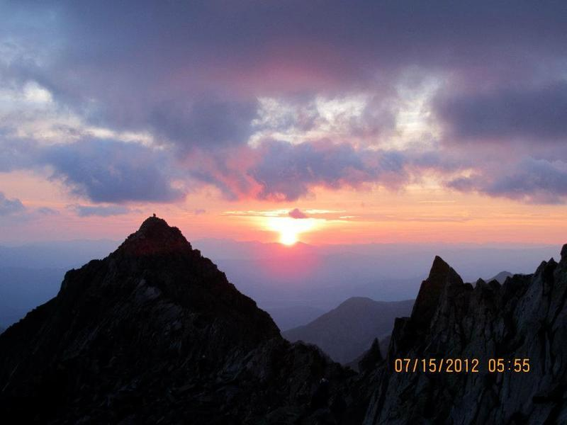 Taken from across the knife edge, this picture shows a hiker on top of K2, with a stunning sunrise behind him.