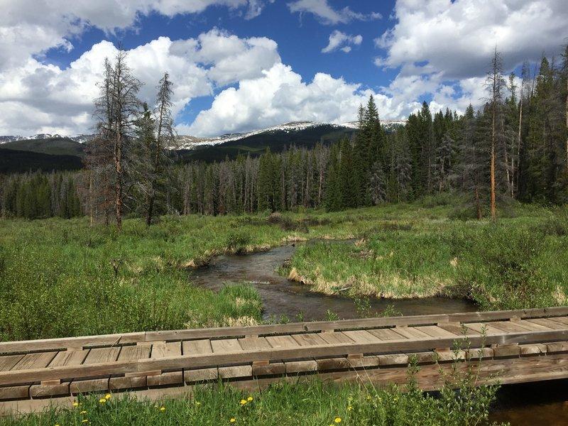 Bridge crossing with meadow and Indian Peak views