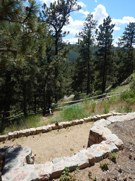 """The start of the Prairie Overlook Trail is just south past this """"notch"""" in the ramp wall.  Cross the wood fence and head southwest along a faint trail that gradually becomes more visible.  See cairns in this picture."""