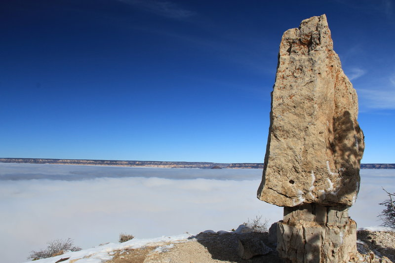 Tombstone rock on Shoshone Point with inversion cloud layer in the canyon