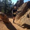 Still below treeline nearly halfway to Pikes Peak summit, a runner enjoys a short mellow section of Barr Trail with some funky formations. Photo by Nancy Hobbs