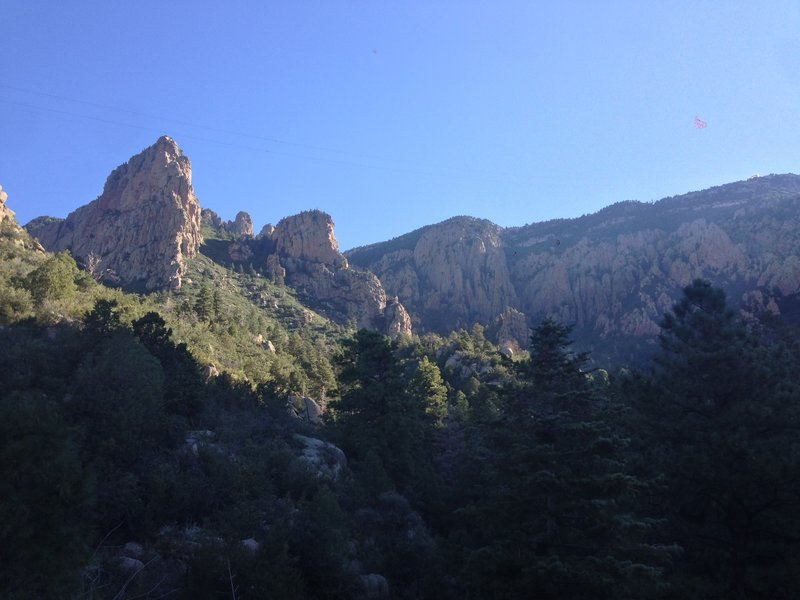 The view of the Sandia ridgeline from the trail, with the tramway cables visible overhead. The upper station of the tramway is visible on the right side of the picture. The crash site is at the base of the large rock formation on the left.