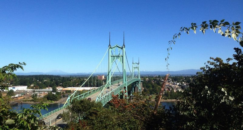 The lower end of the Ridge Trail offers a stunning view of the St. Johns Bridge and the Cascade Range. Mt. St. Helens can be seen on the left side of the bridge and Mt. Adams on the right.