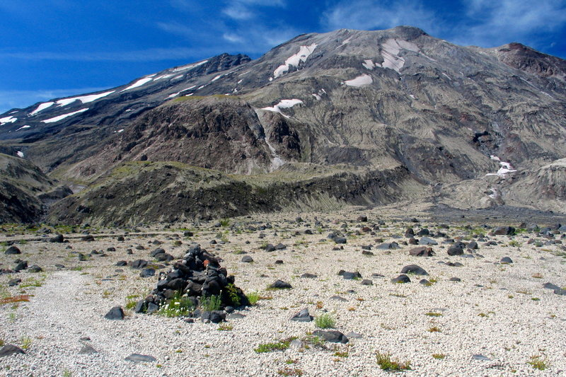 A rock cairn marks the route with Mt. St. Helens in the background.