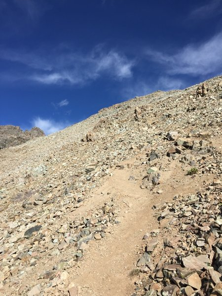 After rounding the ridge, continue on loose trail before reaching the rocky, scrambly area.