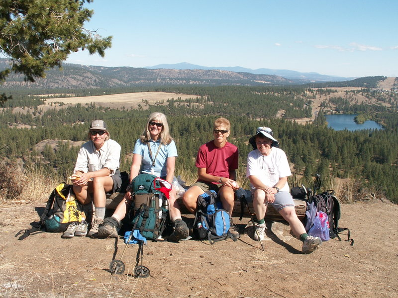 Hikers enjoying the bench with the view at the top of Pine Bluff.  Spokane River in the distance.