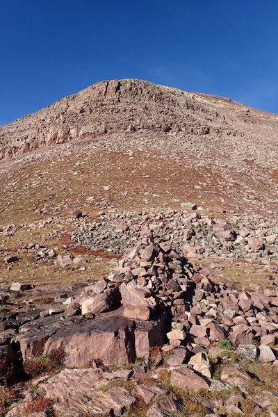 The large rock cairn at Gunsight Pass.  In the background is the cliff band that runs beneath West Gunsight Peak (Dome Peak).