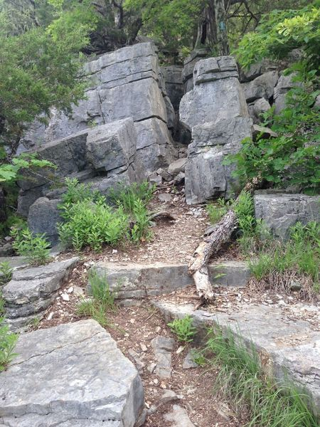 The trail pinches in between rocks.