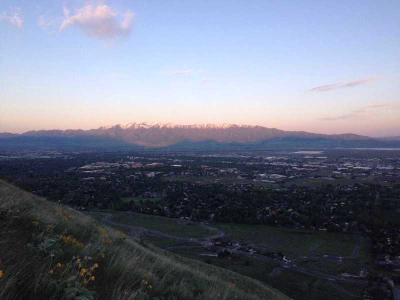 A view of the sunrise over the Wellsville mountains with the shadows of the Bear River Range just below them, and then Cache Valley in the forefront, all witnessed from the Saddleback Mountain Trail.