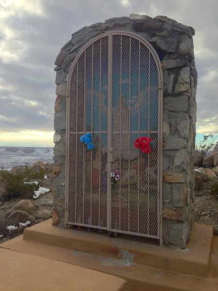 One of the trail's shrines, this one to the Virgin of Fatima. It is kept locked on non-event days. In the distance, the border fence can be seen crawling up the mesa, marking the international boundary.